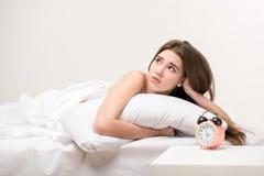 Schönheit, die auf dem Bett mit einer Uhr liegt Stockfotos