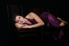 Schönheit, die auf ihrer Seite in einem purpurroten Kleid liegt Stockfotografie