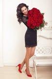 Schönheit mit dem dunklen Haar, das mit einem großen Blumenstrauß von Rosen aufwirft Lizenzfreies Stockbild