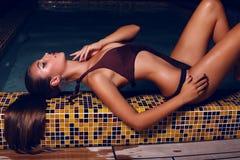 Schönheit mit dem dunklen Haar im Bikini, der im Nachtswimmingpool aufwirft Stockfotografie