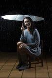 Schönheit mit dem silbernen Kleid, das unter einem Regenschirm an n sitzt Stockfotografie