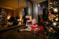 Schönheiten nahe bei Weihnachtsbaum Stockfotos