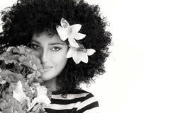 Schönheits-Gesicht mit wilder gelockter Afro-Frisur mit Blumen Stockfoto