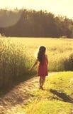 Schönheits-Mädchen, das draußen Natur genießt Schönes kleines Mädchen im roten Kleid, das auf dem Frühlings-Feld läuft getont Stockbild