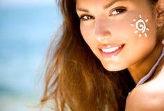 Schönheits-Mädchen mit Sun Tan Cream auf ihrem Gesicht Stockfotos