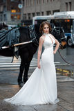 Schönheitsbraut im langen weißen Hochzeitskleid, das in New- York Citystraße aufwirft Stockbild
