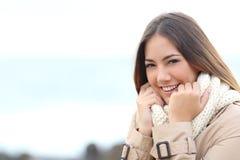 Schönheitsfrau, die ihren Schal im Winter lächelt und ergreift Stockbild