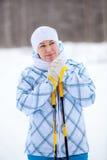 Schönheitsfrau mit den gefrorenen Händen mit Skipfosten Stockfotografie