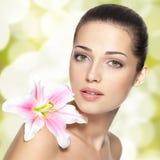 Schönheitsgesicht der jungen Frau mit Blume. Schönheitsbehandlungskonzept Stockbild