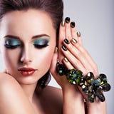 Schönheitsgesicht mit Make-up und Glasschmuck, kreative Nägel Stockbilder