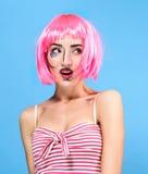 Schönheitshauptschuß Überraschte junge Frau mit kreativer Pop-Art bilden und zacken die Perücke aus, welche die Kamera auf blauem Stockfotografie