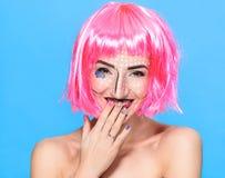 Schönheitshauptschuß Nette junge Frau mit kreativer Pop-Art bilden und zacken die Perücke aus, welche die Kamera auf blauem Hinte Stockbild