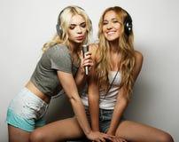 Schönheitsmädchen mit einem Mikrofon singend und tanzend Lizenzfreie Stockfotografie