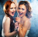 Schönheitsmädchen mit einem Mikrofon singend und tanzend Lizenzfreies Stockfoto
