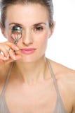 Schönheitsporträt der Frau, die Wimperlockenwickler verwendet Stockbild