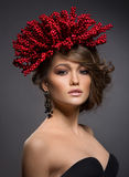Schönheitsporträt des hübschen europäischen Mädchens mit roten Beeren von Viburnum auf Kopf als Frisur Stockfotos