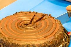Schnitt der ersten Paare der Scheiben aus einem Schokoladenkuchen heraus Stockbild