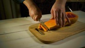 Schnitt der geschmackvollen Kürbisscheibe Männliche Hände, die Lebensmittelkürbis für das Kochen zubereiten stock video