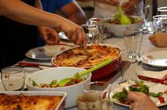 Schnitt der Lasagne während der Familienmahlzeit Stockfotografie