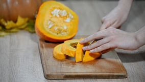Schnitt der rohen Kürbisscheibe Frau, die orange Kürbisstück schneidet Roher Kürbisschnitt stock video footage