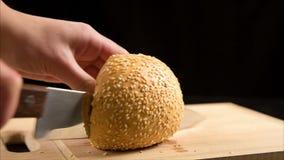 Schnitt des Brötchens mit Samen des indischen Sesams mit einem Küchenmesser auf hölzernem