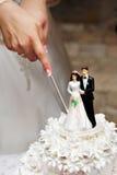 Schnitt des Hochzeitskuchens Stockbilder