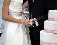 Schnitt des Hochzeitskuchens Stockfotos
