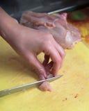 Schnitt des Huhns auf einem gelben Brett Stockbild