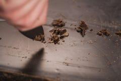 Schnitt des industriellen Blockes der dunklen Schokolade mit Messer Stockbilder