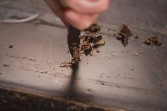 Schnitt des industriellen Blockes der dunklen Schokolade mit Messer Lizenzfreie Stockbilder