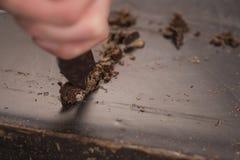 Schnitt des industriellen Blockes der dunklen Schokolade mit Messer Stockfotos