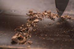 Schnitt des industriellen Blockes der dunklen Schokolade mit Messer Stockfoto