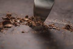Schnitt des industriellen Blockes der dunklen Schokolade mit Messer Stockbild
