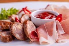 Schnitt des Speckes, der Wurst, des Prosciutto und des kurierten Fleisches auf einer feierlichen Tabelle stockfotos