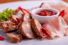 Schnitt des Speckes, der Wurst, des Prosciutto und des kurierten Fleisches auf einer feierlichen Tabelle stockbilder