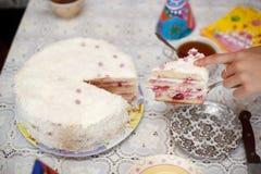 Schnitt des weißen Erdbeerkuchens mit einem Messer Lizenzfreie Stockfotografie