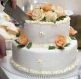 Schnitt einer weißen Hochzeitstorte Stockfotos