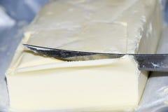 Schnitt eines Buttermessers Butter und Messer Lizenzfreie Stockbilder