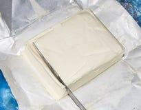 Schnitt eines Buttermessers Butter und Messer Stockfoto