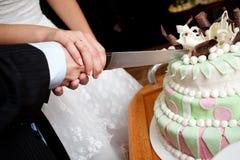 Schnitt eines Hochzeitskuchens Lizenzfreie Stockbilder