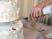 Schnitt eines Hochzeitskuchens Lizenzfreie Stockfotos