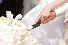 Schnitt eines Hochzeitskuchens Stockfotos