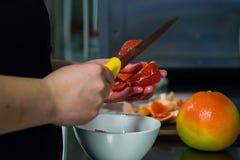 Schnitt von grupefriut durch Chef der Küche lizenzfreies stockfoto