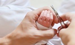Schnitt von neugeborenen Babynägeln mit Scheren stockfoto