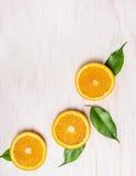Schnitt von orange Früchten mit Blättern auf weißem hölzernem Hintergrund Lizenzfreies Stockfoto