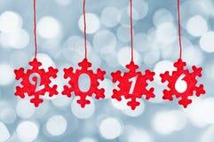 2016 schnitten in die roten Gewebeweihnachtsverzierungen, die am bokeh hängen Lizenzfreies Stockbild