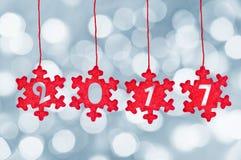 2017 schnitten in die roten Gewebeweihnachtsverzierungen, die an bokeh Hintergrund, Dekoration des neuen Jahres hängen Stockfotos