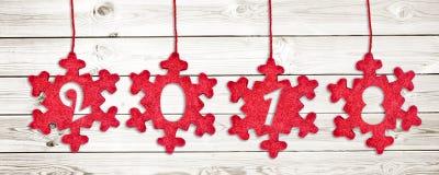 2018 schnitten in die roten Gewebeweihnachtsverzierungen, die am weißen hölzernen Plankenhintergrund hängen Lizenzfreie Stockfotografie