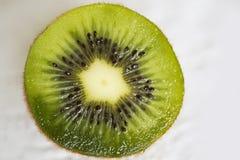 Schnittgrünfruchtkiwi mit schwarzen Samen und weißem Kern Stockbild