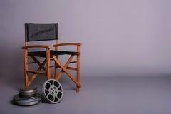 Der Stuhl des Filmregisseurs mit Filmspule Stockfotos
